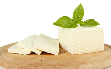 Sheep milk cheese with basil on cutting board, isolated on