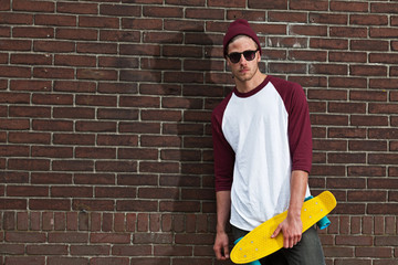 Urban fashion skateboarder with woolen hat and sunglasses in fro