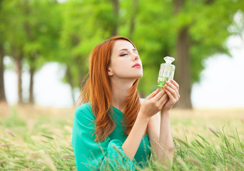 Redhead girl with perfume at outdoor