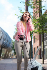 Woman walking dog and calling by phone outdoors