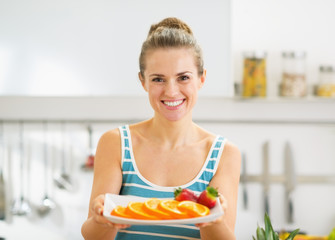 Happy young woman holding plate with strawberry and orange