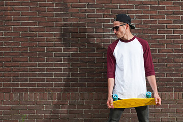 Urban fashion skateboarder with black cap and sunglasses in fron Wall mural