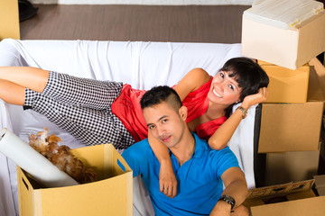 Asian couple having break while moving in