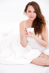 portrait of  woman in bed holding a cup