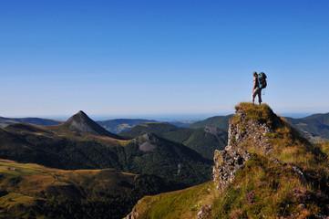 hiker on top of a rock looking far away Wall mural