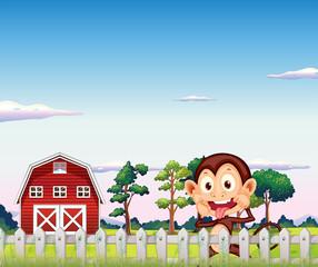A monkey near the red barnhouse
