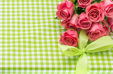 fresh pink roses over green gift background