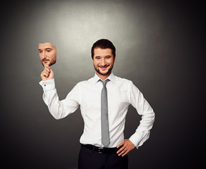businessman holding serious mask