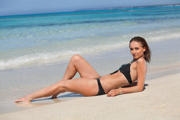 attraktive junge frau mit schwarzem bikini am strand