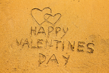 In the beach sand: Happy Valentine's Day and two hearts