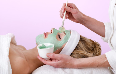 Beautician applying a thalasso face mask.