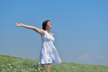young woman with spreading arms to sky