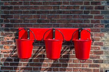 Three red fire buckets wall mounted
