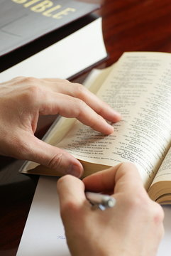 Detail of hands with pen and open Bible