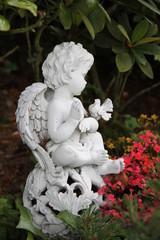 Kleiner Engel mit Taube sitzt auf bepflanztem Grab