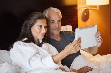 Couple watching movie on a digital tablet in a hotel room