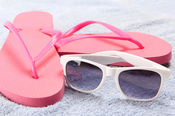 red flip flops and sunglasses over towel