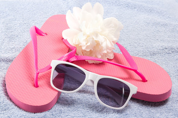 red flip flops, sunglasses and flower over towel