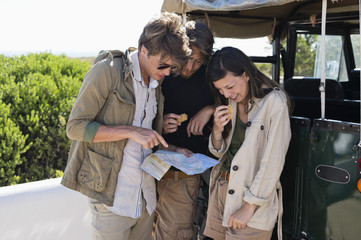 Friends looking at map beside a SUV