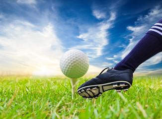 foot kicking golf ball on tee