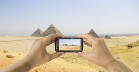 tourist holds up camera mobile at  pyramids