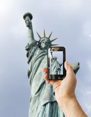 tourist holds up camera phone at  statue of liberty