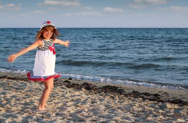 Wall Mural - beautiful happy little girl on beach