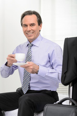 Restoring his energy. Cheerful mature businessman drinking coffe