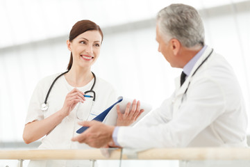 Consulting with colleague. Female doctor communicating with her
