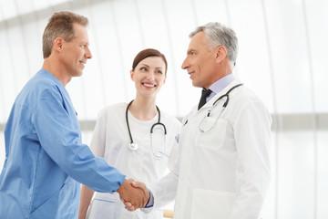 Welcome on board! Two mature doctors handshaking while  beautifu