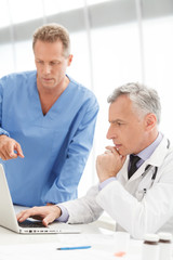 Discussing medical reports. Mature doctor using computer and dis