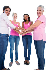 Happy women wearing breast cancer ribbons putting hands together