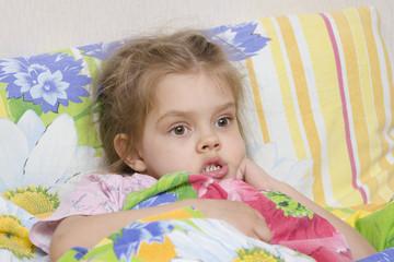 Четырехлетняя девочка лежит в кровати накрывшись одеялом