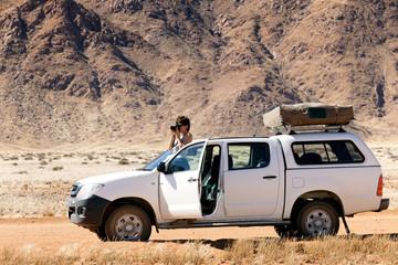 photographer on safari in Africa on his car