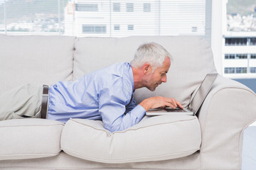 Businessman lying on couch with laptop