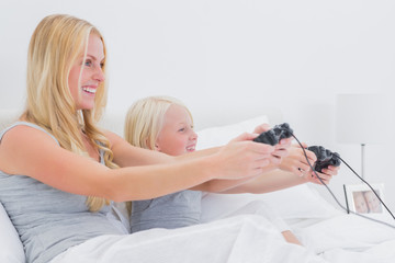 Mother and daughter having fun playing video games