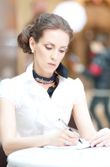 Businesswoman writing with pen in organizer