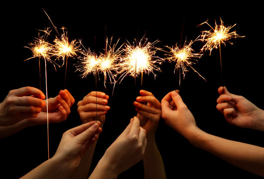 beautiful sparklers in hands on black background.