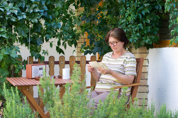 Old woman watching photos in garden