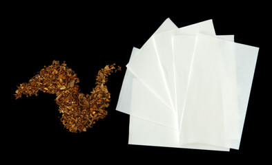 Tobacco and rolling paper, isolated on black