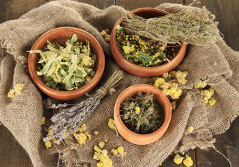 Medicinal Herbs in wooden bowls on bagging close-up
