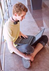 Teenage boy using internet sitting in commercial center floor