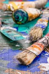 Pinsel, Spachtel und Ölfarben auf einer Holzpalette
