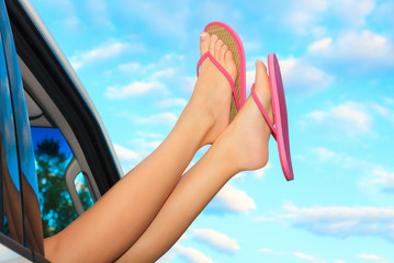 Female legs in pink sandals out from the car