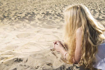 Woman in dress draw hearts on sand