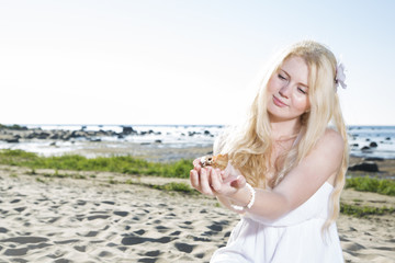 Young woman hold clam at her hands
