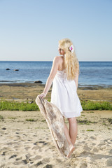 Young woman walking with scarf at beach