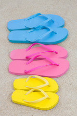 colorful beach flip flops on sand