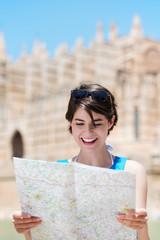 lächelnde frau liest landkarte im urlaub