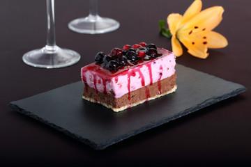 dessert con frutti di bosco su pietra nera sfondo porpora